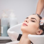 Revel in rest. Pleasant beautiful woman leaning on the sing while professional hairdresser washing her head